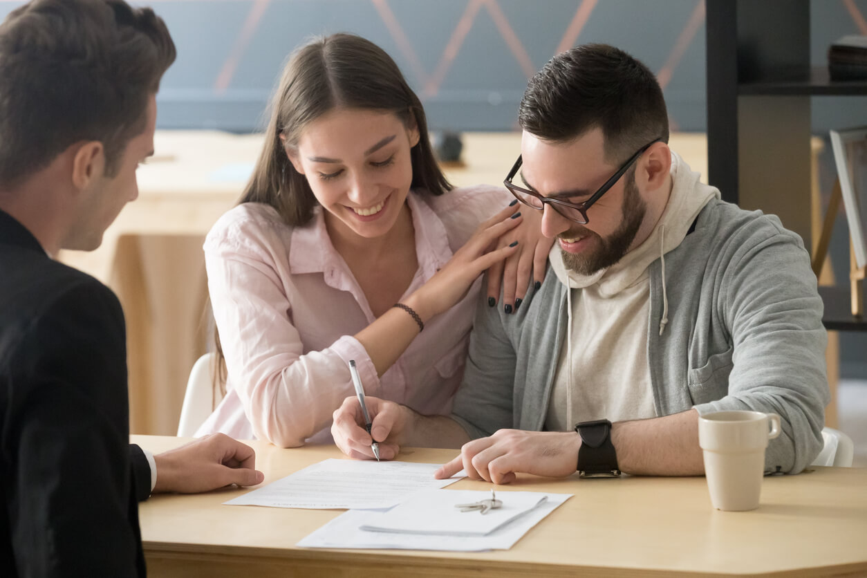happy young couple buying a house for the first time and signing papers on closing day with agent