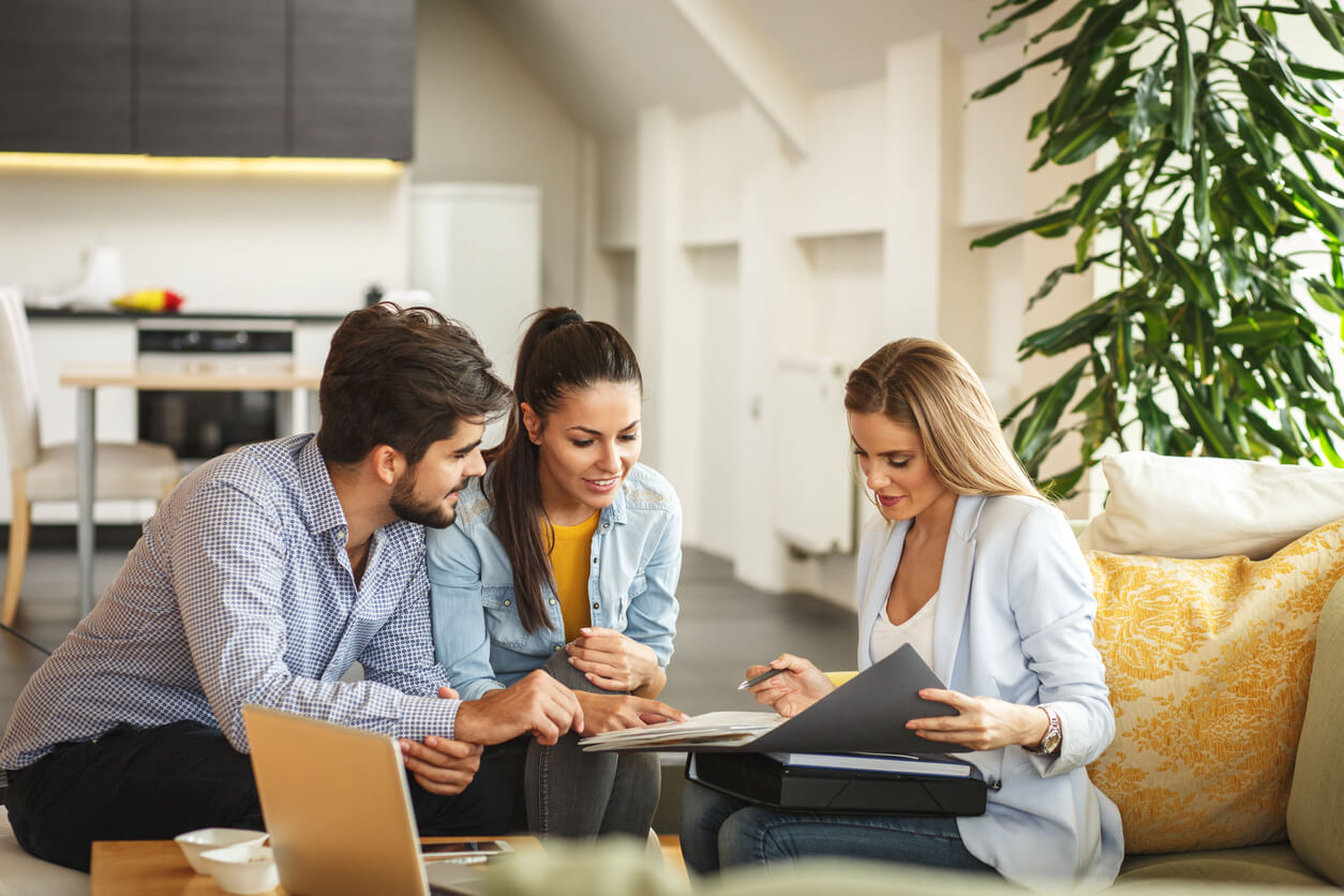 Female real estate or listing agent helping young couple buy or sell a house