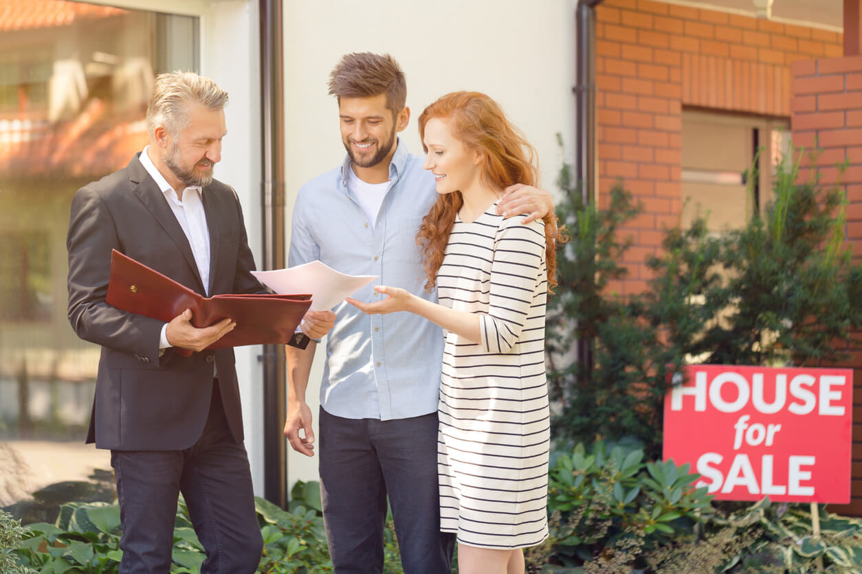 Agent talking to a couple in front of a house for sale, sell your home concept