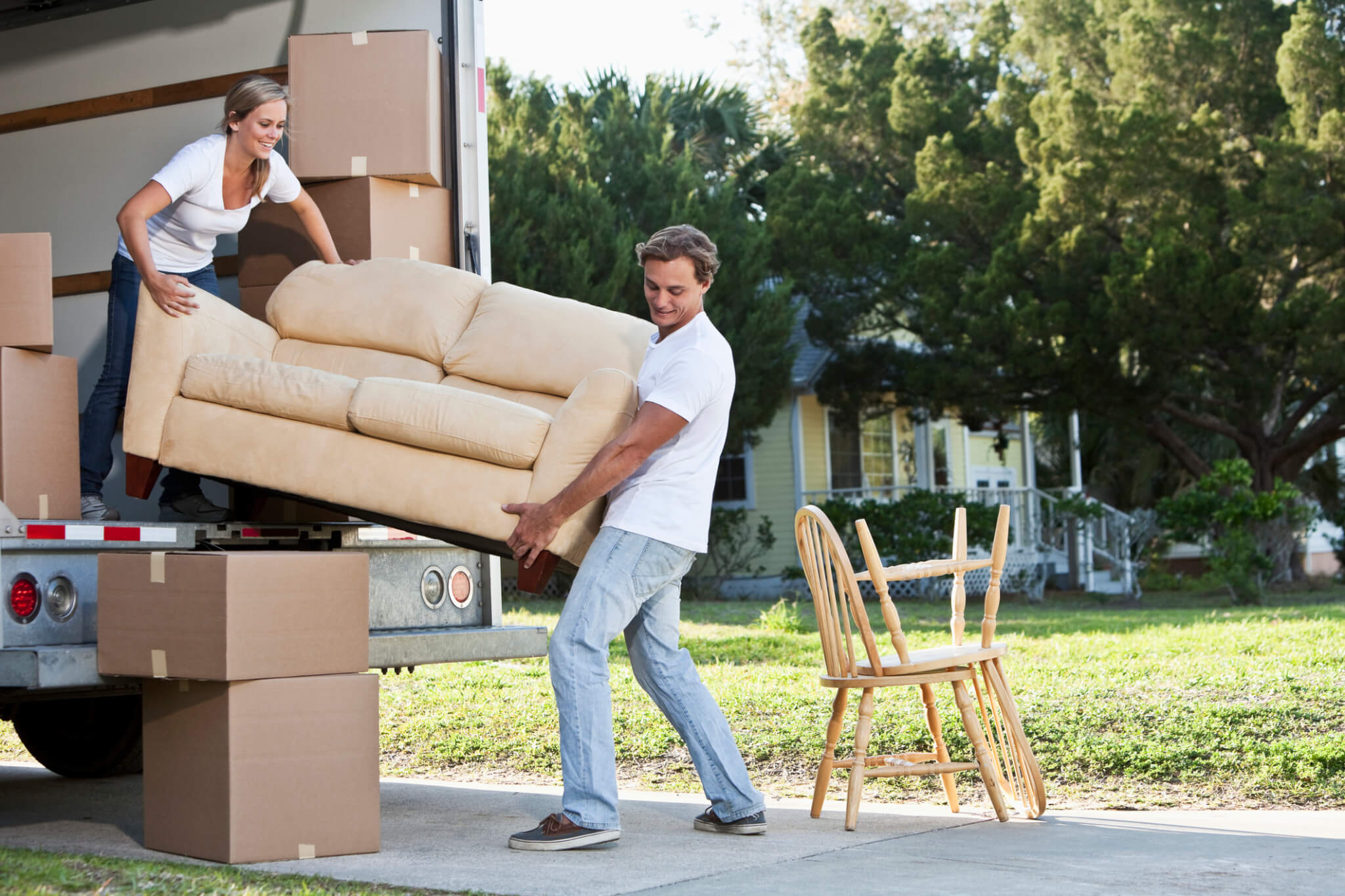 Young couple moving to a new house and packing a move-in truck