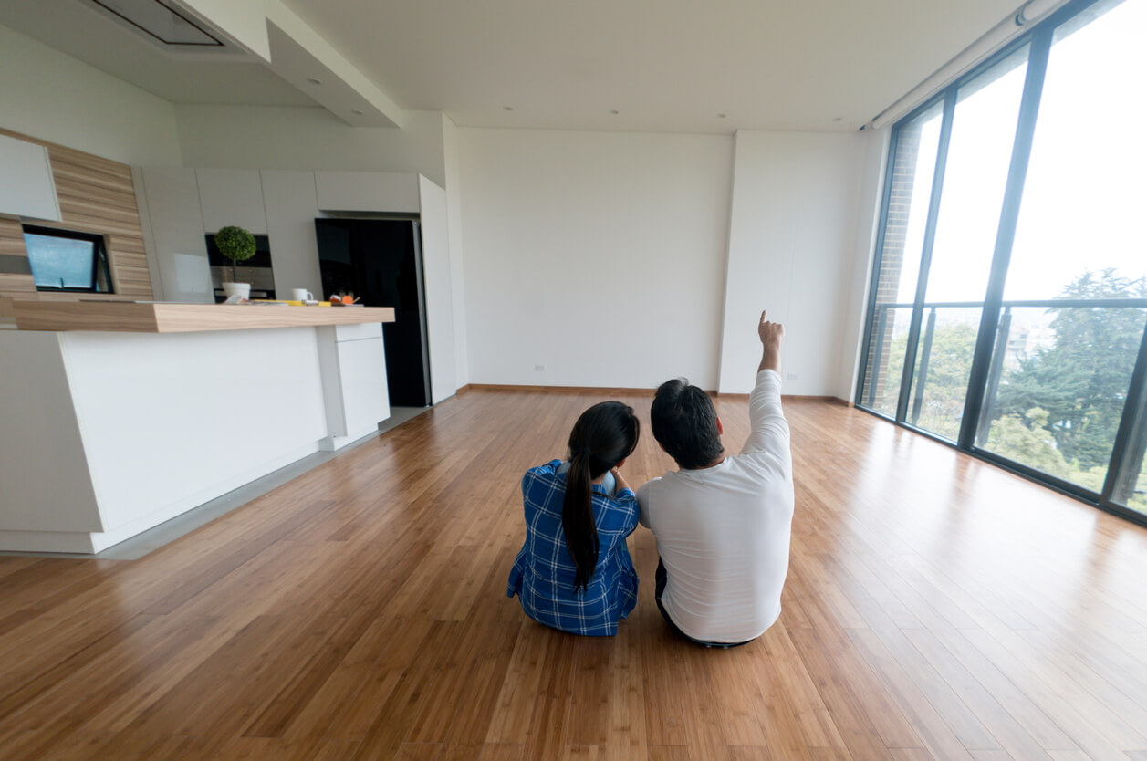 A couple sitting in their new house, owning a home concept