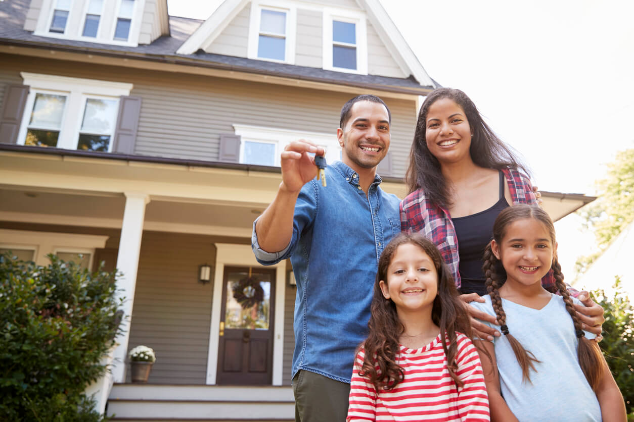 Happy family outside of their newly-bought home, considering home buying guide.