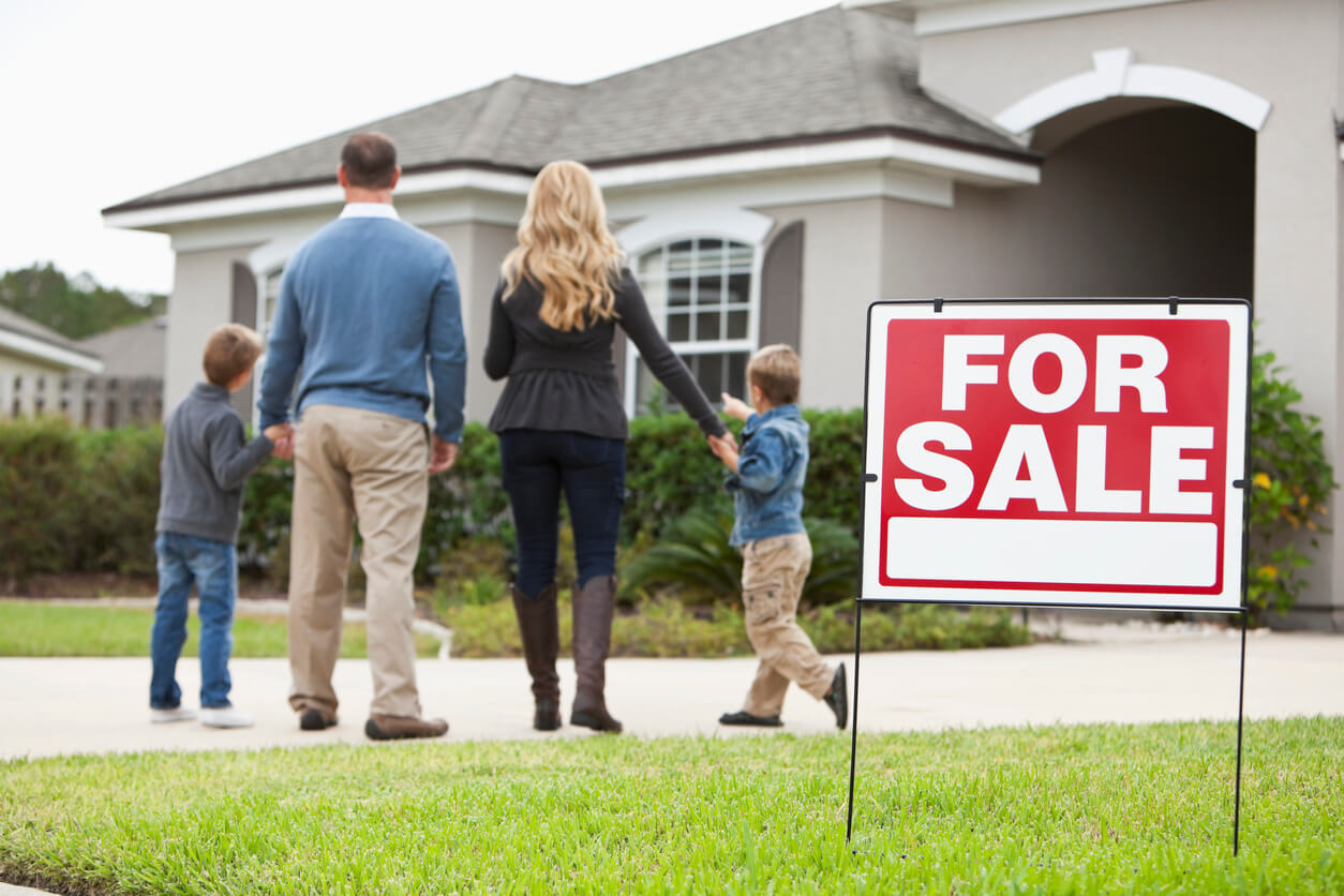 Family with two boys (4 and 6 years) standing in front of house with FOR SALE sign in front yard. Focus on sign.