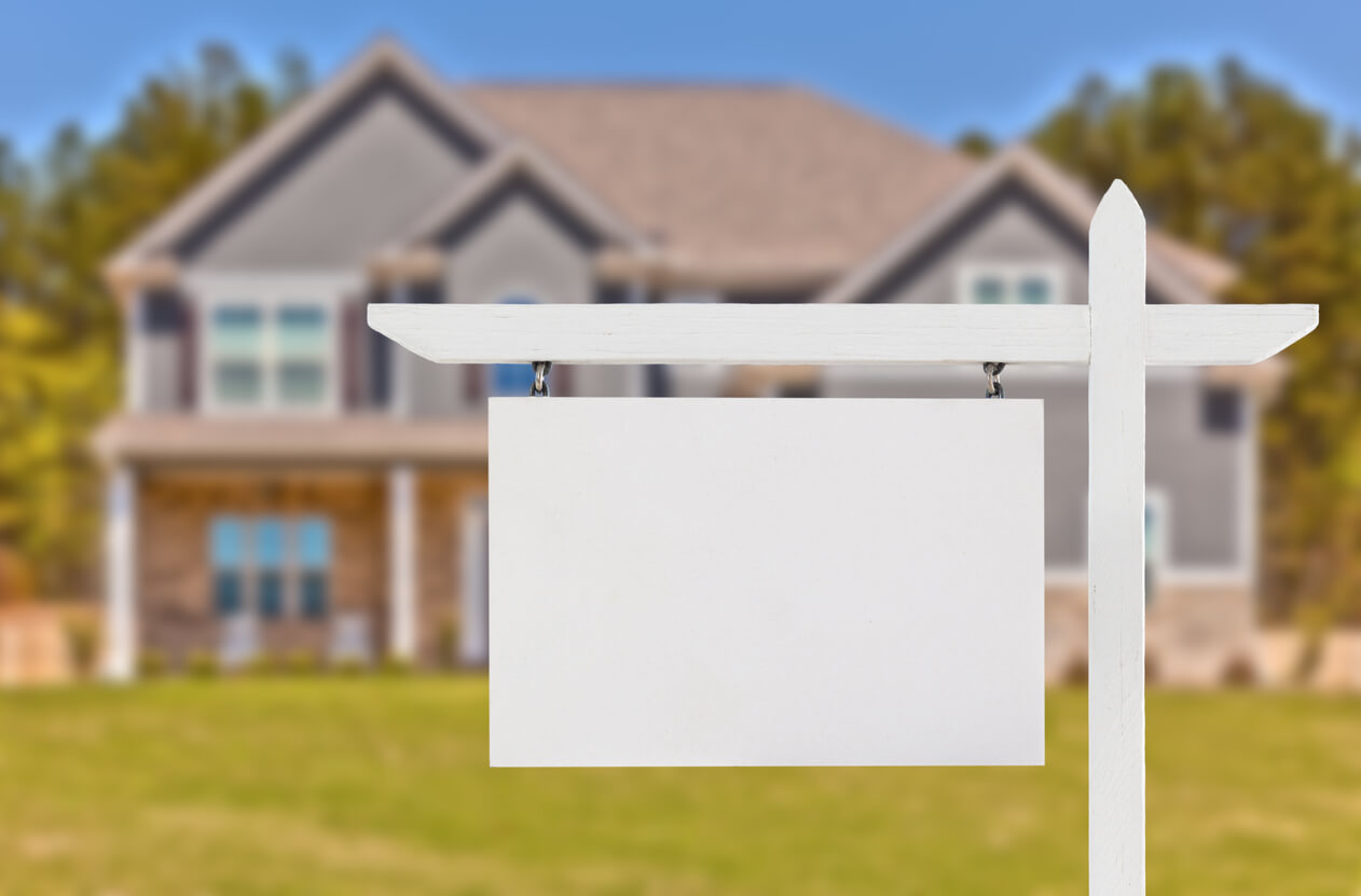 blank real estate sign in front of house | SIGNATURE PROPERTIES GROUP