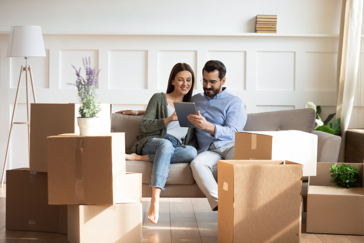 Couple sitting on a couch while using a tablet device to look for a property during their home buying process.